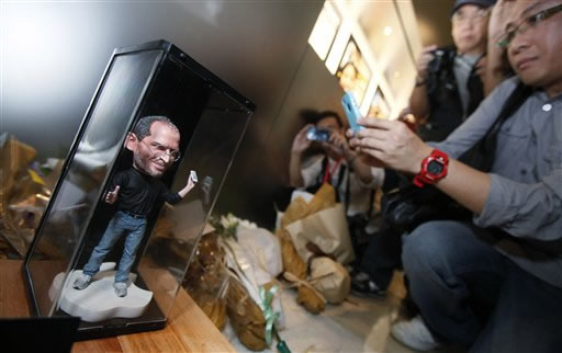 "<div class=""meta image-caption""><div class=""origin-logo origin-image ""><span></span></div><span class=""caption-text"">A man takes pictures of a figure of Apple founder and former CEO Steve Jobs near flowers laid in his tribute at an Apple retail store in Hong Kong Thursday, Oct. 6, 2011. Jobs, the co-founder of Apple Inc. and father of the iPhone, has died at age 56. (AP Photo/Kin Cheung)</span></div>"