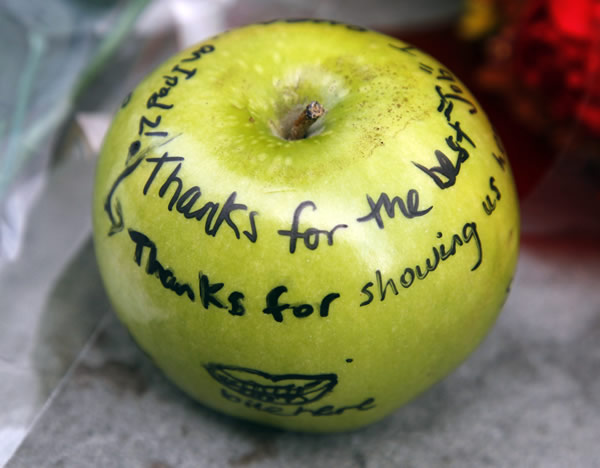 An apple with tributes written on it is part of a memorial for Apple co-founder Steve Jobs on the sidewalk in front of an Apple store, in Boston, Thursday, Oct. 6, 2011. Jobs died Wednesday at 56. <span class=meta>(AP Photo&#47;Steven Senne)</span>