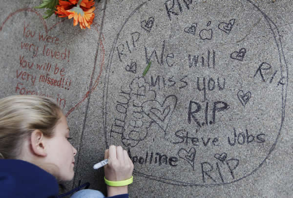 Apolline Arnaud, 12, a neighbor of Steve Jobs, writes a message in front of Jobs&#39; home in Palo Alto, Calif., Wednesday, Oct. 5, 2011. Jobs, the Apple founder and former CEO who invented and masterfully marketed ever-sleeker gadgets that transformed everyday technology, from the personal computer to the iPod and iPhone, has died. He was 56. <span class=meta>(AP Photo&#47;Paul Sakuma)</span>