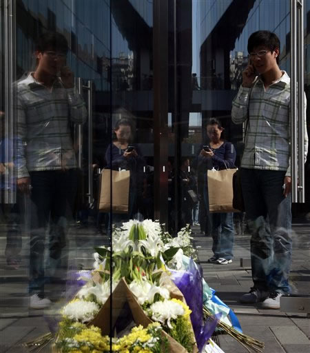 A Chinese man and woman use Apple&#39;s iPhones near flowers laid in tribute to Steve Jobs outside an Apple retail store in Beijing, China, Thursday, Oct. 6, 2011. Steve Jobs, the co-founder of Apple Inc. and father of the iPhone, has died at age 56. <span class=meta>(AP Photo&#47;Ng Han Guan)</span>