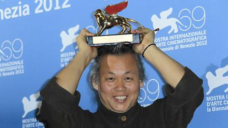 Director KIM ki-duk shows the Golden Lion he won for his movie Pieta at the awards photo call during the 69th edition of the Venice Film Festival in Venice, Italy, Saturday, Sept. 8, 2012. (AP Photo/Joel Ryan)