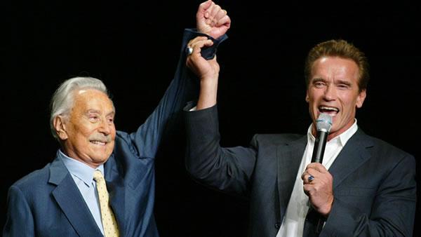 California Gov.-elect Arnold Schwarzenegger, right, raises the arm of Joe Weider