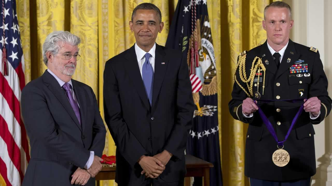 President Barack Obama stands with director George Lucas as he awards him the 2012 National Medal of Arts during a ceremony in the East Room of White House.