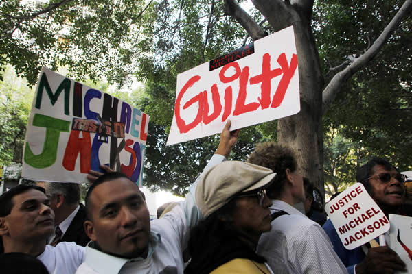 People hold up signs outside the Criminal Justice Center in downtown Los Angeles, Monday, Nov. 7, 2011 after it was announced that jurors had reached a verdict in the involuntary manslaughter trial of Dr. Conrad Murray, Michael Jackson&#39;s physician when the pop star died in 2009. <span class=meta>( AP Photo&#47;Danny Moloshok)</span>