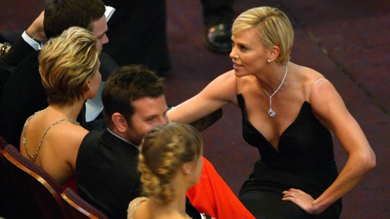 Charlize Theron, right, talks to Jennifer Lawrence in the audience at the Oscars.