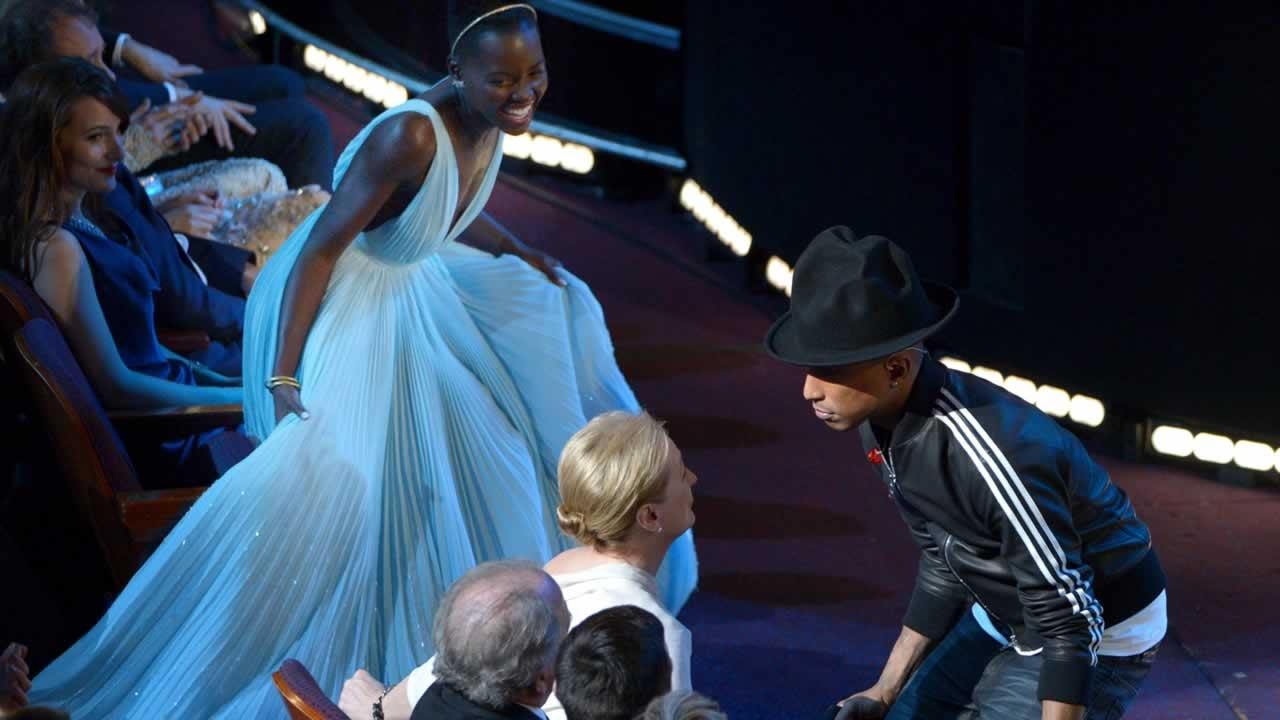 Lupita Nyongo , left, looks on as Meryl Streep dances with Pharrell Williams during his performance of Happy at the Oscars.