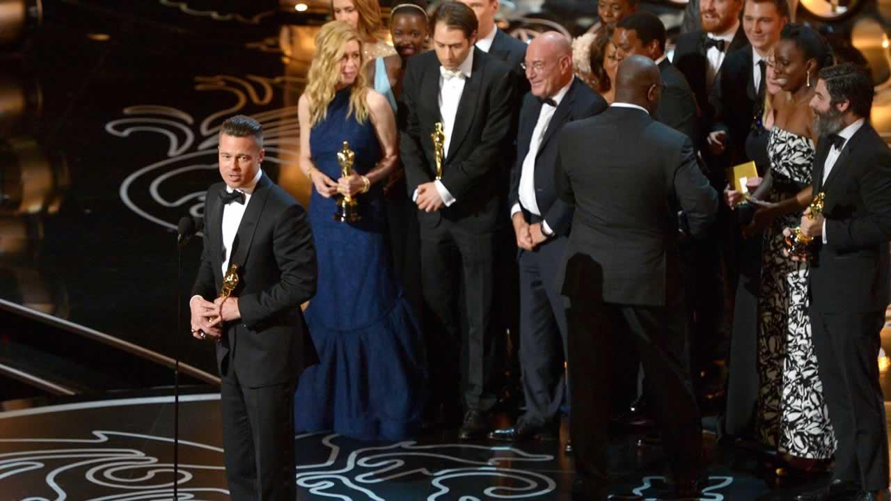 Brad Pitt, left, speaks as he and the cast and crew of 12 Years a Slave accept the award for the best picture during the Oscars.