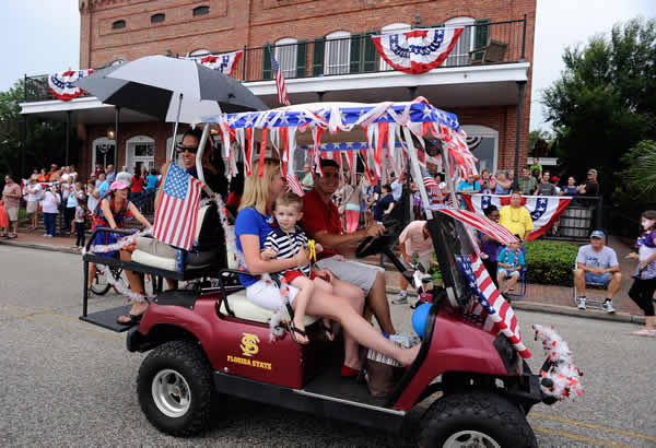 Golf carts and bicycles helped lead an Independence Day celebration that included a parade down historic Water Street adjacent to the Apalachicola River on Wednesday, July 3, 2013, in Apalachicola, Fla. (AP Photo/David Tulis)