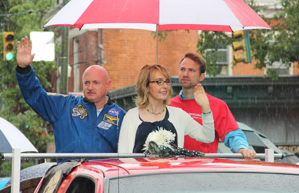 Former U.S. Rep. Gabrielle Giffords and husband, former astronaut Mark Kelly, ride in the back of a truck as they take part in a parade in Northside, a suburb of Cincinnati, Thursday, July 4, 2013, on their Rights and Responsibilities Tour. Giffords and Kelly are co-founders of the gun violence prevention group Americans for Responsible Solutions. (AP Photo/Tom Uhlman)