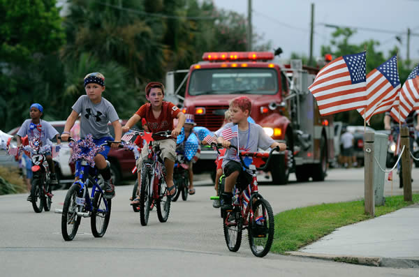 Children on bicycles lead a parade down Water Street next to the Apalachicola River during an Independence Day celebration that included live bands in front of the city's fishing fleet, an ice cream social at Riverfront Park and a fireworks display Wednesday, July 3, 2013, in Apalachicola, Fla. (AP Photo/David Tulis)