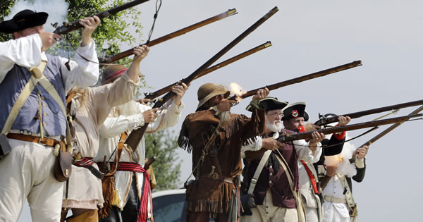 Members of a Living History Musket Detail fire a volley during a Fourth of July Patriotic Ceremony at Fort Sam Houston National Ceme