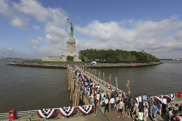 Visitors to the Statue of Liberty disembark onto Liberty Island from the first ferry to leave Manhattan, Thursday, July 4, 2013 at in New York. The Statue of Liberty finally reopened on the Fourth of July months after Superstorm Sandy swamped its little island in New York Harbor as Americans across the country marked the holiday with fireworks and barbecues. (AP Photo/Mary Altaffer)