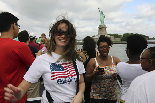 Visitors to fhe Statue of Liberty take photos as they arrive on the first tourist ferry to leave Manhattan, Thursday, July 4,