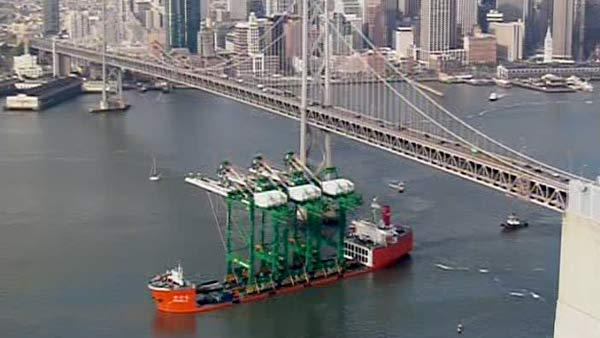 A ship carrying three new container cranes passed under the Bay Bridge.
