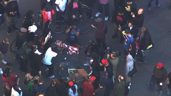 Demonstrators in Oakland set an American flag on fire d