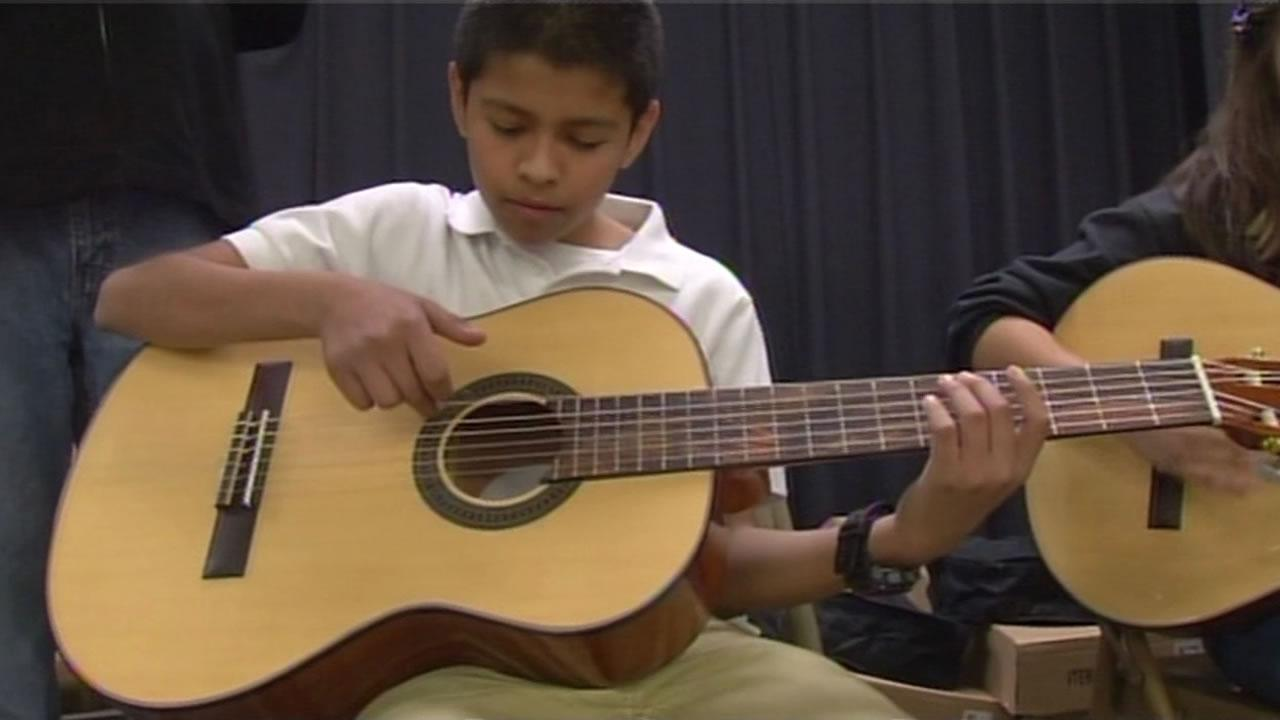 A student plays a guitar at a San Jose middle school.