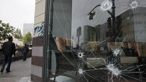 People walk past the smashed windows of a Sears store in Oakland, Calif., Friday, July 9, 2010.