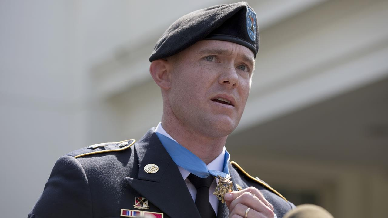US Army Staff Sgt. Ty M. Carter speaks to the media and his holds Medal of Honor outside the West Wing of the White House in Washington, Monday, Aug. 26, 2013, after President Barack Obama presented it inside.