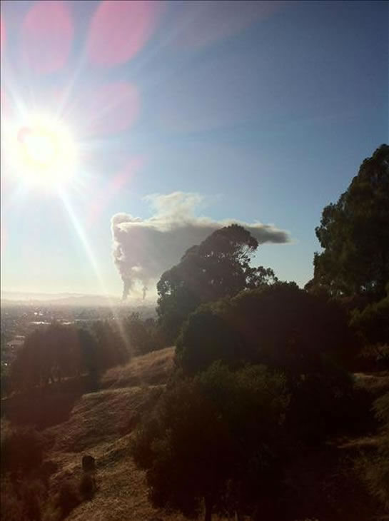 A visible fire could be seen burning at the Chevron Refinery in Richmond and a large black plume of smoke. This is a view from the El Cerrito Hills right after the alarm sounded.  (Photo sent in by a viewer via uReport)