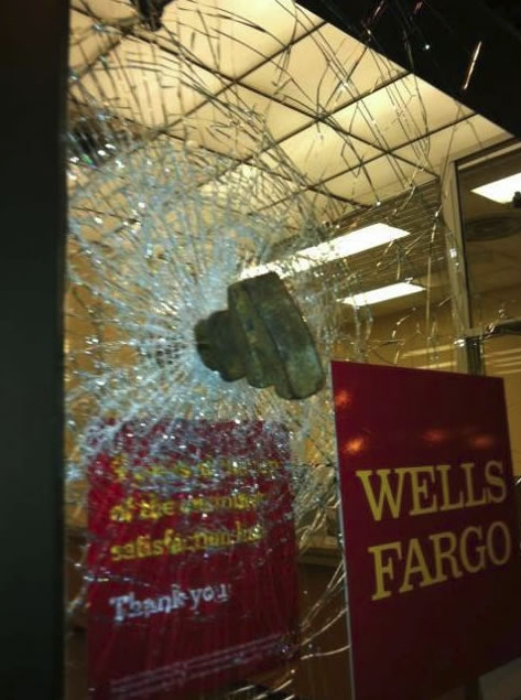Oakland police officers and protesters clashed during a May Day march in downtown Oakland. Some protesters smashed the windows of a Wells Fargo and threw a wrench into the glass. (May 1, 2012/KGO)
