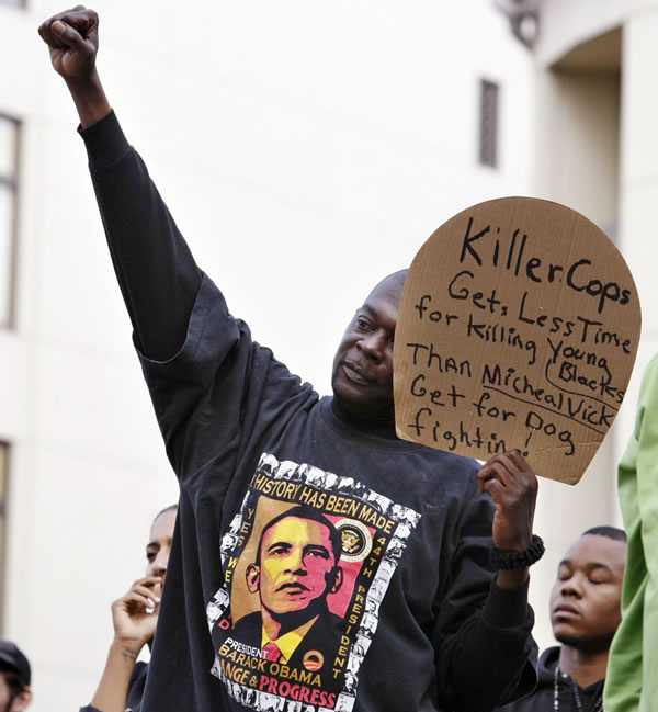 Demonstrator Gregory Nash holds a sign after the sentencing of former Bay Area Rapid Transit police officer Johannes Mehserle in Oakland, Calif., Friday, Nov. 5, 2010. Mehserle was convicted of involuntary manslaughter for the fatal shooting of Oscar Grant at a BART station on Jan. 1, 2009. Los Angeles Superior Court Judge Robert Perry sentenced Mehserle  to two years in prison. (AP Photo/Paul Sakuma)
