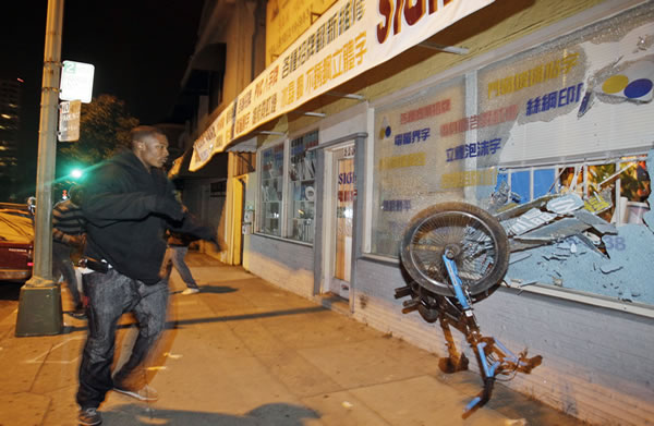 A demonstrator breaks a storefront window with a bike during street protests in reaction to the conviction of Bay Area Rapid Transit police officer Johannes Mehserle in Oakland, Calif., Friday, Nov. 5, 2010. Mehserle was convicted of involuntary manslaughter for the fatal shooting of Oscar Grant at a BART station on Jan. 1, 2009. Los Angeles Superior Court Judge Robert Perry sentenced Mehserle to two years in prison. (AP Photo/Marcio Jose Sanchez)