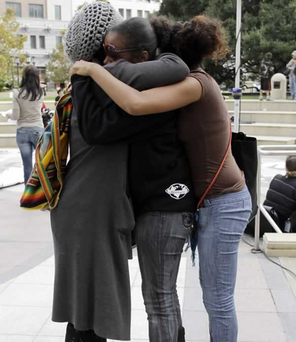 Three people hug as they are upset after the sentencing of former Bay Area Rapid Transit police officer Johannes Mehserle. in Oakland, Calif., Friday, Oct. 5, 2010. Los Angeles Superior Court Judge Robert Perry sentenced former Bay Area Rapid Transit police officer Johannes Mehserle to two years in prison the fatal shooting of Oscar Grant at a BART station on Jan. 1, 2009. (AP Photo/Paul Sakuma)