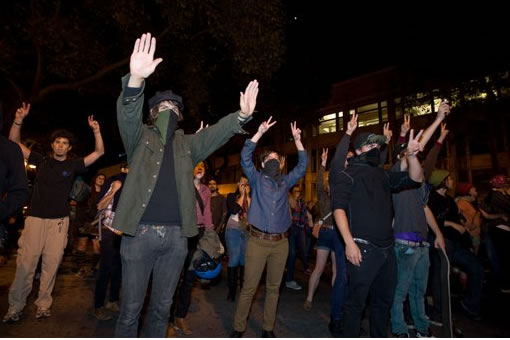 Occupy Wall Street protesters raise their hands and chant after they were dispersed by police deploying tear gas at 14th and Broadway Streets in Oakland, Calif., Tuesday, Oct. 25, 2011. (AP Photo/Darryl Bush)