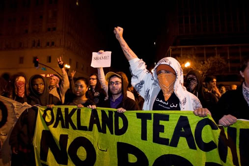 Occupy Wall Street protesters yell towards police stopping their path at 14th and Broadway Streets in Oakland, Calif., Tuesday, October 25, 2011. (AP Photo/Darryl Bush)