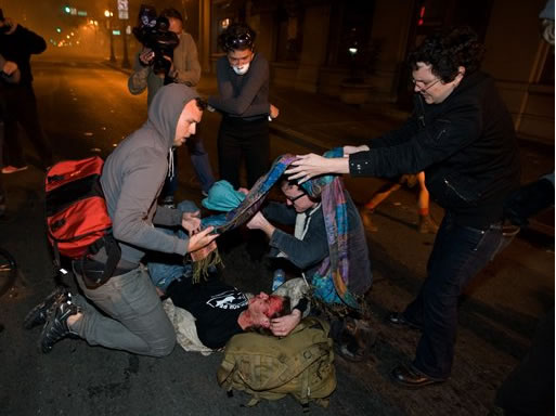 Occupy Wall Street protesters help a man injured after police used tear gas to disperse a large crowd of protesters at 14th Street and Broadway in Oakland, Calif., Tuesday, Oct. 25, 2011. (AP Photo/Darryl Bush)