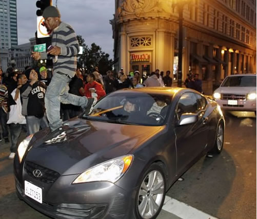 A demonstrator jumps on a car after the sentencing of former Bay Area Rapid Transit police officer Johannes Mehserle in Oakland, Calif., Friday, Nov. 5, 2010. Mehserle was convicted of involuntary manslaughter for the fatal shooting of Oscar Grant at a BART station on Jan. 1, 2009. Los Angeles Superior Court Judge Robert Perry sentenced Mehserle  to two years in prison. (AP Photo/Paul Sakuma)