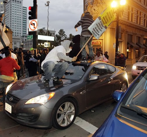 Two demonstrators jump on a car after the sentencing of former Bay Area Rapid Transit police officer Johannes Mehserle in Oakland, Calif., Friday, Nov. 5, 2010. Mehserle was convicted of involuntary manslaughter for the fatal shooting of Oscar Grant at a BART station on Jan. 1, 2009. Los Angeles Superior Court Judge Robert Perry sentenced Mehserle  to two years in prison. (AP Photo/Paul Sakuma)