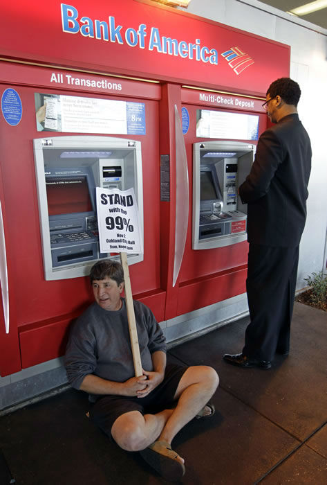 A protesters sits in front of an ATM machine as a customer gets money at a Bank of America branch in Oakland, Calif., Wedsesday, Nov. 2, 2011. Thousands of anti-Wall Street protesters are in the streets of Oakland, Calif., as part of a day-long series of events aimed at showing the movement's strength and unity. (AP Photo/Paul Sakuma)
