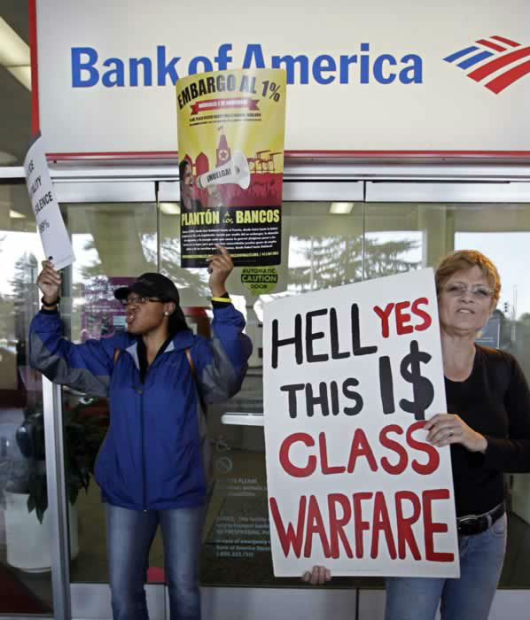 Tanya White, left, former customer of Bank of America, and an unidentified fellow protester block the door of a Bank of America branch in Oakland, Calif., Weds., Nov. 2, 2011. Thousands of anti-Wall Street protesters are in the streets of Oakland, Calif., as part of a day-long series of events aimed at showing the movement's strength and unity. (AP Photo/Paul Sakuma)