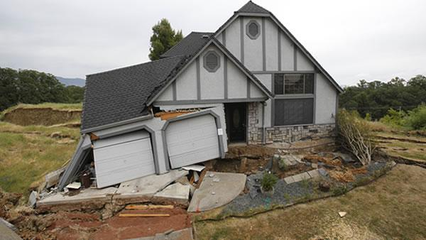 This photo taken Monday, May 6, 2013 shows the wreckage of the Tudor-style dream home of Robin and Scott Spivey who were forced to abandon after the ground gave way causing it to drop 10 feet below the street in Lakeport, Calif.