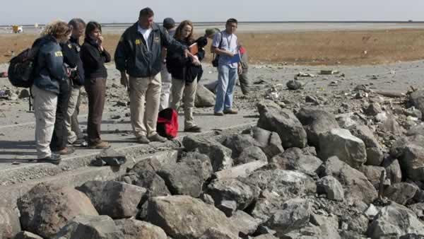 NTSB investigator Brian Murphy shows the depth of the debris field to NTSB team.