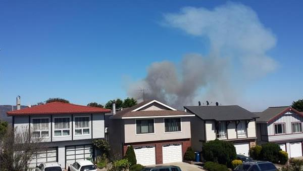 A four-alarm fire burning on San Bruno Mountain in South San Francisco sent a large plume of smoke in the air that was visible from several miles away. (Photo submitted via uReport by Almira)