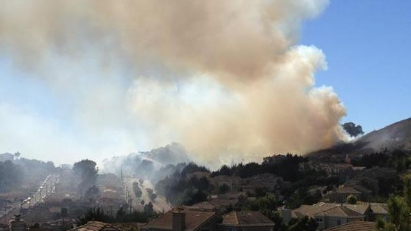 A four-alarm fire burning on San Bruno Mountain in South San Francisco sent a large plume of smoke in the air that was visible from several miles away. (Photo submitted via uReport by an anonymous viewer)