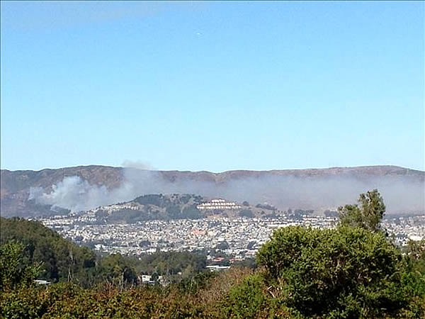 A four-alarm fire burning on San Bruno Mountain in South San Francisco sent a large plume of smoke in the air that was visible from several miles away. (Photo submitted via uReport by anonymous user)