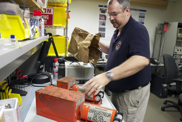 NTSB Aerospace Engineer Greg Smith receiveing the recorders from the Asiana Airlines Flight 214 in the NTSB laboratory in Washington