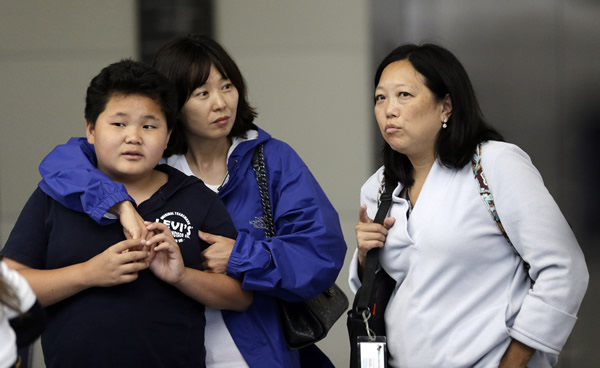 <span class=meta>(Onlookers talk outside of The Reflection Room where friends and relatives of Asiana Flight 214 passengers await news following the plane crash. Saturday,July 6, 2013. &#40;AP Photo&#47;Marcio Jose Sanchez&#41;)</span>