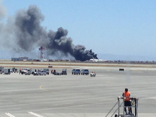 This photo provided by Krista Seiden shows smoke rising from what a federal aviation official says was an Asiana Airlines flight crashing while landing at San Francisco airport on Saturday, July 6, 2013. It was not immediately known whether there were any injuries. (AP Photo/Krista Seiden)