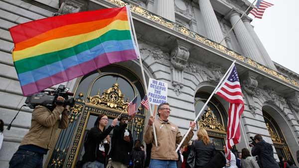 Billy Bradford of Castro Valley, Calif., waves a pair of flags outside City Hall while same-sex couple line up to see if they can be married in San Francisco, Thursday, August 12, 2010.