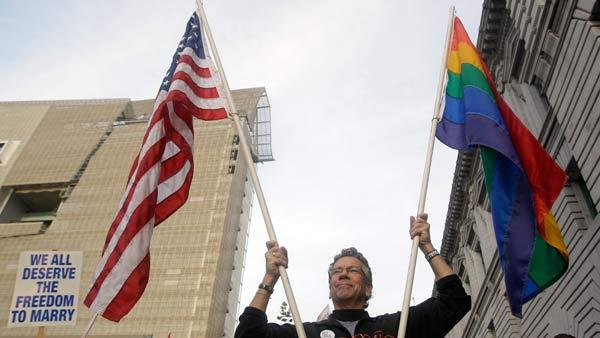 Billy Bradford carries an American flag and a rainbow flag before a hearing in the Ninth Circuit Court of Appeals, Monday, Dec. 6, 2010, in San Francisco.