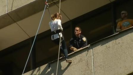 woman rapelling down building