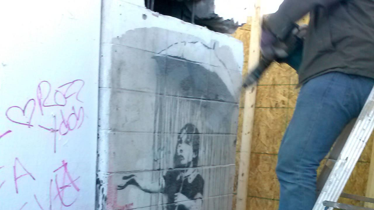 In this Friday, Feb. 21, 2014 photo provided by Mohan Choppala, an unidentified man cuts into a wall with a mural created by the artist Banksy, in New Orleans
