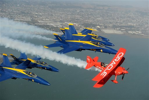 In preparation for Fleet Week performances, the U.S. Navy Blue Angels and Team Oracle stunt pilot Sean D. Tucker fly over the San Francisco Bay on Thursday, Oct. 4, 2012. <span class=meta>(AP Photo&#47;Noah Berger)</span>