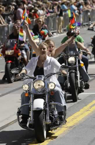 A woman holds up rainbow flags from the back of a motorcycle during the 41st annual Gay Pride parade in San Francisco, Sunday, June 26, 2011. (AP Photo/Jeff Chiu)