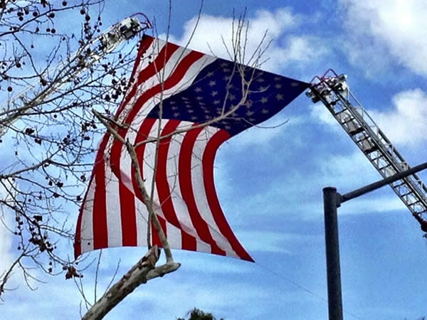 Flag hanging from Santa Cruz and San Jose fire ladders at HP Pavilion for Santa Cruz fallen police officers memorial service. <span class=meta>(KGO)</span>