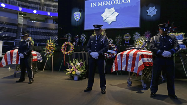 Police stand guard over the caskets of slain Santa Cruz police Sgt. Loran Baker and detective Elizabeth Butler lie at a memorial service Thursday, March 7, 2013, at HP Pavilion in San Jose, Calif. Baker and Butler were shot to death on Feb. 27, after arriving at the home of Jeremy Peter Goulet to question him about a misdemeanor sexual assault. (AP Photo/Ben Margot)